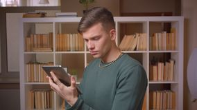 Portret van het jonge mannelijke student werken aandachtig met tablet die aandachtig en geinteresseerd bij bibliotheek zijn stock footage