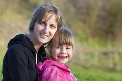 Portret van het jonge mooie blonde meisje koesteren veel liefs en beschermend haar kleine peuter tandenloze zuster, allebei die h Royalty-vrije Stock Foto