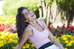 Portret van het jonge mooie maniervrouw lachen op een bloemenachtergrond stock afbeeldingen