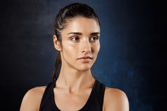 Portret van het jonge mooie sportieve meisje stellen over donkere achtergrond Stock Afbeelding