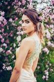 Portret van het jonge mooie vrouw stellen in de bomen van de de lentebloesem Royalty-vrije Stock Fotografie