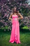 Portret van het jonge mooie vrouw stellen in de bomen van de de lentebloesem Stock Foto