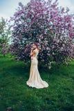 Portret van het jonge mooie vrouw stellen in de bomen van de de lentebloesem Royalty-vrije Stock Foto's