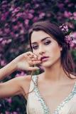 Portret van het jonge mooie vrouw stellen onder de bomen van de de lentebloesem Stock Foto