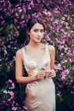 Portret van het jonge mooie vrouw stellen onder de bomen van de de lentebloesem Royalty-vrije Stock Foto's