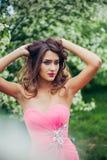 Portret van het jonge mooie vrouw stellen onder de bomen van de de lentebloesem Royalty-vrije Stock Foto
