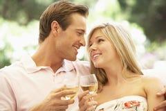 Portret van het Jonge Paar Ontspannen op Sofa Drinking Wine Together Stock Afbeelding
