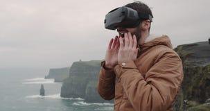 Portret van het jonge stuk speelgoed spelen met een VR op de bovenkant van Klippen met verbazend landschap, maakte indruk hij zee stock video