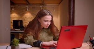 Portret van het jonge tiener werken met laptop die optimistisch en positief in bureau zijn stock video