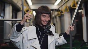 Portret van het jonge vrouw dragen in laag met hoofdtelefoons die aan muziek luisteren en het grappige dansen in openbaar vervoer stock video