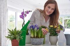 Portret van het Jonge Vrouw Geven voor Houseplants binnen stock foto