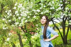 Portret van het jonge vrouw glimlachen in de gebloeide tuin in de de lentetijd Apple-de boom bloeit bloesems stock fotografie