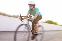 Portret van het jonge vrouwelijke atleet rennen op een fiets. motie blurre Stock Fotografie