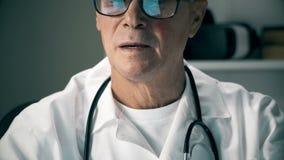 Portret van het Kaukasische midden oude arts werken bij laptop computer op zijn medisch kantoor Hij past langs zijn glazen aan stock video