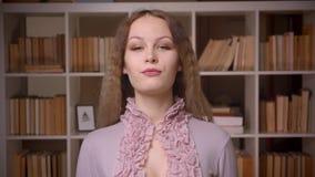 Portret van het Kaukasische wavy-haired blondeleraar letten op calmly en vast in camera bij bibliotheek stock videobeelden