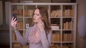Portret van het Kaukasische wavy-haired blondeleraar spreken in videochat op smartphone smilingly bij bibliotheek stock video