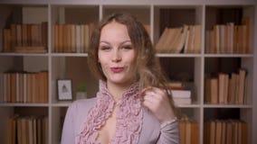 Portret van het Kaukasische wavy-haired blondeleraar stellen gelukkig en seductively in camera bij bibliotheek stock video