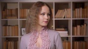 Portret van het Kaukasische wavy-haired blondeleraar stellen schuchter en seductively in camera bij bibliotheek stock videobeelden
