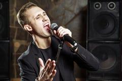 Portret van het knappe aantrekkelijke zanger zingen geraakt met open mond in microfoon royalty-vrije stock fotografie
