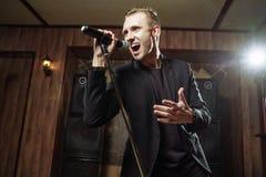Portret van het knappe aantrekkelijke zanger zingen geraakt met open mond in microfoon stock afbeelding