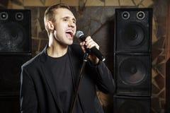Portret van het knappe aantrekkelijke zanger zingen geraakt met open mond in microfoon royalty-vrije stock afbeeldingen