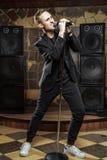 Portret van het knappe aantrekkelijke zanger zingen in microfoon royalty-vrije stock foto