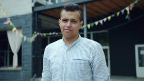 Portret van het knappe Arabische student glimlachen in de straat die zich in openlucht bevinden stock videobeelden