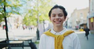Portret van het knappe jongen glimlachen die camera bekijken die zich in de alleen straat bevinden stock video