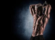 Portret van het knappe spierbodybuilder stellen over zwarte bedelaars stock foto's
