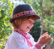 Portret van het lachen weinig jongen in een wit geborduurd overhemd en een hoed stock afbeelding