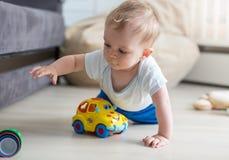 Portret van het leuke babyjongen kruipen op vloer en het spelen met stuk speelgoed stock foto's