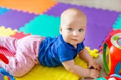 Portret van het leuke die babyjongen liggen op vloer met multicolored zachte matten wordt behandeld in speelkamer Aanbiddelijk en stock fotografie