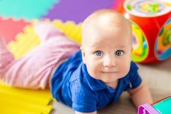 Portret van het leuke die babyjongen liggen op vloer met multicolored zachte matten wordt behandeld in speelkamer Aanbiddelijk en stock foto