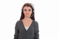 Portret van het leuke donkerbruine die meisje van de call centrearbeider met hoofdtelefoons en microfoon op witte achtergrond wor Stock Foto's