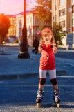Portret van het leuke meisje die zich in rolschaatsen in het stad-park in warme sunshiny dag bevinden royalty-vrije stock foto's