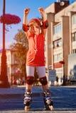Portret van het leuke meisje die zich in rolschaatsen in het stad-park in warme sunshiny dag bevinden stock foto