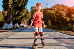 Portret van het leuke meisje die zich in rolschaatsen in het stad-park in warme sunshiny dag bevinden stock afbeeldingen