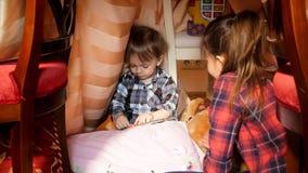 Portret van het leuke peuterjongen spelen met oudere zuster in tent bij slaapkamer royalty-vrije stock foto's