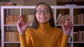 Portret van het modieuze donkerbruine vrouwelijke leraar bidden met kruisen-vingers die voor geluk bij de bibliotheek hopen stock video