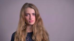 Portret van het mooie blonde Kaukasische jonge vrouw letten op in camera en negatief het draaien van haar hoofd op grijs stock footage