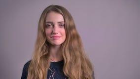Portret van het mooie blonde Kaukasische jonge vrouw letten smilingly op in camera en het wenken op grijze achtergrond stock footage