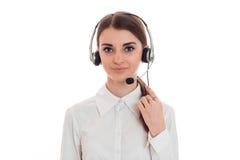 Portret van het mooie donkerbruine die meisje van de call centrearbeider met hoofdtelefoons en microfoon op witte achtergrond wor Stock Foto