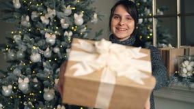 Portret van het mooie donkerbruine geven huidig op Kerstmisdag die binnen zich thuis met verfraaide Nieuwjaarboom bevinden en stock videobeelden