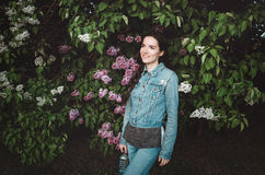 Portret van het mooie glimlachen, jonge vrouw openlucht met bloesem purpere lilac bloemen in de lentetuin aantrekkelijk Stock Foto's