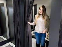 Portret van het mooie het glimlachen jonge vrouw proberen op warme wolsweater in winkelcomplexkleedkamer royalty-vrije stock foto