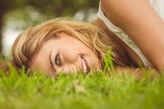 Portret van het mooie het glimlachen vrouw liggen op gras stock afbeelding