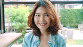 Portret van het Mooie jonge Aziatische donkerbruine vrouw glimlachen terwijl status in koffie Het concept van de vrouwenlevenssti stock video