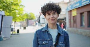 Portret van het mooie jonge damestudent glimlachen die zich in openlucht in de straat bevinden stock video