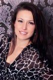 Portret van het mooie jonge donkerbruine glimlachmeisje in zwarte kleding Stock Foto