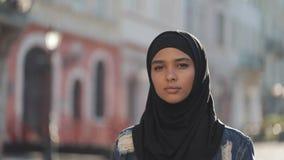 Portret van het mooie jonge Moslimvrouw dragen die hijab headscarf de camera onderzoeken die op de oude stad lopen stock videobeelden